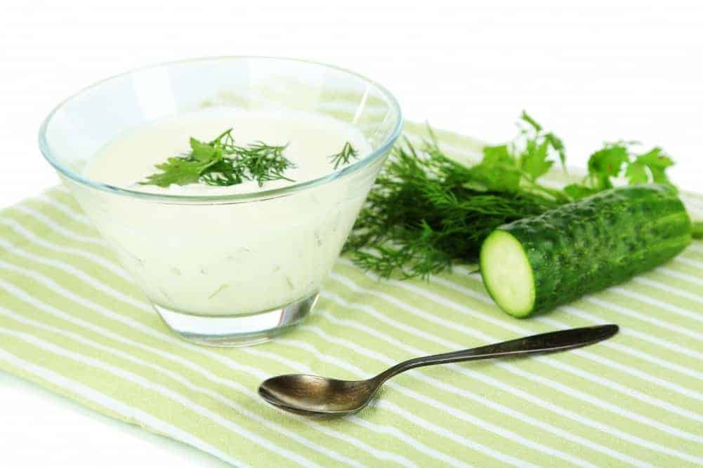 Cucumber yogurt in glass bowl, on color napkin, isolated on white
