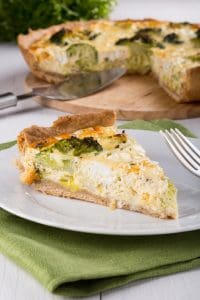 Quiche with broccoli and cheese on a white plate. Piece of homemade vegetable pie.