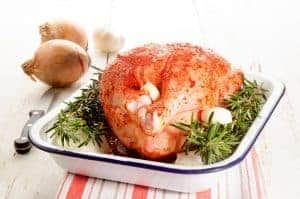 raw chicken with a marinade made of paprika powder, onion, garlic and rosemary