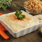 Hummus with vegetables and breads on a wooden table