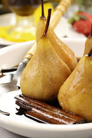 Delicious poached pears with a cinnamon stick in syrup.