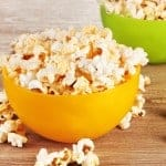 popcorn in bright plastic bowls on wooden table