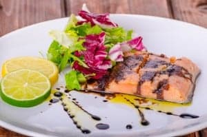 Salmon with a reduction of balsamic vinegar and sugar, fresh salad, lemon lime